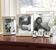 simple display--silver frames grouped on table (with white flowers)  BW pics.