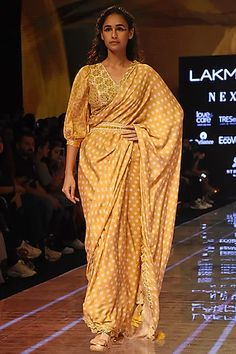 Featuring a mustard saree in satin silk base with bandhani print and mirror embellished border. It is paired with a matching blouse having mirror work. FIT: True to size. CARE: Dry clean only. Rekha Saree, Rahul Khanna, Samant Chauhan, Bandhani Saree, Krishna Janmashtami, Neeta Lulla, Indian Fashion Designers, Manish Malhotra, Mirror Work