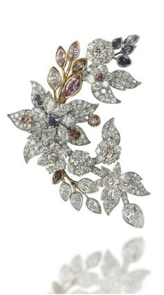 A DIAMOND AND COLOURED DIAMOND BROOCH Designed as a spray of flowers and leaves mounted en tremblant, set with vari-cut diamonds and coloured diamonds including tones of pink and purple, mounted in platinum, 6.5 cm