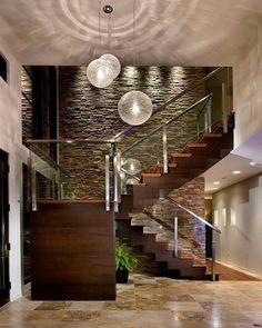 El descanso se extiende generando un espacio intermedio, tipo balcón interior. El espesor de los escalones, aportan seguridad y firmeza. El primer escalón nos da la sensación de que está enterrado en el piso por ser distinto a los demás. El material: la textura de la madera cálida, opaca y lisa al tacto, contrasta con la piedra rugosa, y con el acero y piso, brillosos y fríos. La iluminación rasante realza los materiales y la iluminación general interviene en la doble altura. Es mi preferida!