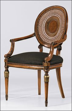 Louis XVI style beechwood armchair with hand-caned back, hand-rubbed antiqued walnut finish, antiqued silverleaf accents and black muslin upholstery