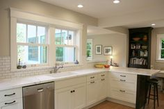 Wide casings and craftsman styling on this pair of windows blend with clean-lined white cabinetry and vintage-inspired hardware to give this California kitchen an elegant, yet casual air. Dark accents on the peninsula and built-ins create contrast, as does the dark wood bookshelf.