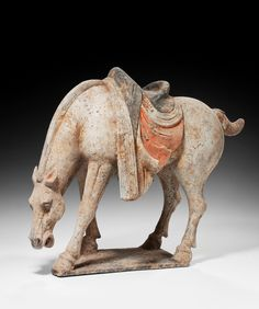 RARE TANG HORSE GRAZING Richard Gardner Antiquesrare figure of a Tang Dynasty horse standing on all four legs with its neck lowered to enable it to graze at the ground below, with a well moulded saddle on its back, which retains some of its original colouring.