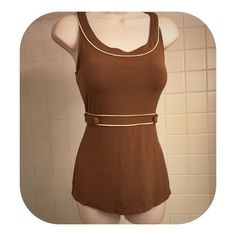 """Cute Brown Sleeveless Top with Cream Piping This cute sleeveless scoop neck brown top by Moth, an Anthropologie brand, has cream colored piping around the neckline and detailing the band that cinched under the bust. The band is adorned with 2 decorative wood buttons. Below the band, the top falls a bit more loosely. This soft & comfortable top is perfect for work or play-or as a layer.  The top is 24.5"""" in length. Preloved, the top is in excellent condition! Anthropologie Tops Tank Tops"""
