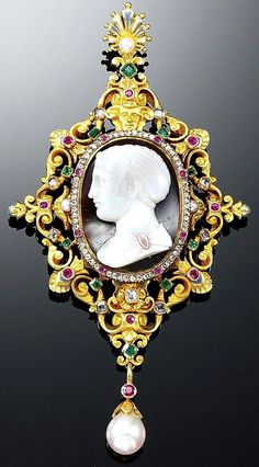 GOLD, HARD STONE ENAMEL AND GEM-SET PENDANT, CIRCA 1880 - In the Renaissance Revival style, the agate cameo of a female profile to the left within a rose-cut diamond and ruby border, the open work gold scroll frame set with step-cut and cushion-shaped rubies, emeralds and diamonds and highlighted with blue and white enamel, embellished by a gargoyle surmounting the cameo and supporting a detachable pearl drop, the reverse engraved with foliate motifs, provided with a pin fitting.