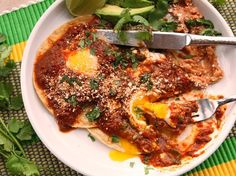 Quick and Easy Huevos Rancheros With Tomato-Chili Salsa | 2 whole dried ancho chiles 1 small yellow onion,  4 medium cloves garlic,  1/2 teaspoon dried oregano, preferably Mexican 1 (14-ounce) can crushed tomatoes, preferably fire-roasted (such as Muir Glen) 2 whole chipotle chiles packed in adobo, plus 2 tablespoons sauce from can 1/4 cup minced fresh cilantro  1 tablespoon soy sauce 1 tablespoon juice from 1 lime,  Up to 12 eggs  Crumbled cotija cheese, for serving Hot refried beans,