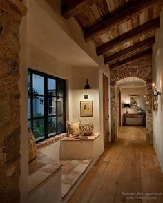 A long corridor with wooden floor and arched stone wall panel design also bay window bench with pillows and lovely wall sconces decor