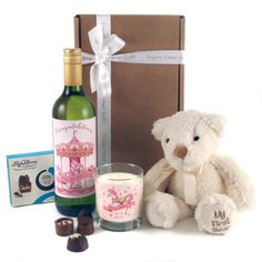 """A Beautiful New Baby Gift Set... Comes with cream plush bear, super soft and embroidered with """"My First Bear"""". For the new parents we've designed and printed labelling for both the wine bottle and the glass candle to make your gift extra special.  Featuring a charming Merry Go Road for both the wine and candle labels together with the wording: """"Congratulations on your New Baby Girl""""."""