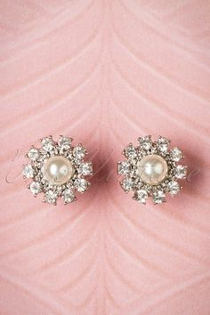 These50sGrace Cream Pearl Stud Earrings are the cream on top of your vintage pie! Classy girls wear pearls, but diamonds are a girls best friend! You'll have the best of both worlds with these classic earstuds. The bigger cream colored faux pearl is being surrounded by dozens of smaller sparkly rhinestones. Classic, elegant and vintage proof!  Little rhinestones faux pearl Silver toned metal Back stoppers