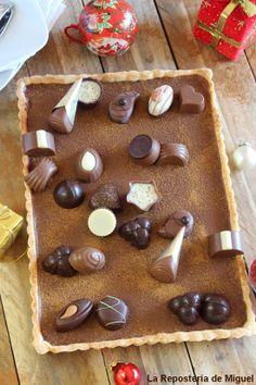 Tarta de masa brisa con relleno de ganaché de chocolate negro y sobre él u surtido de bombones, adornando la mesa de madera bolas y regalos ...