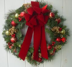 Christmas wreath artificial mixed evergreens with glistening red and gold ornaments,pine cones, gold berry clusters & antique red velvet bow...