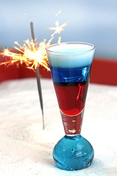 Fourth of July cocktail drink recipe with grenadine, blue curacao and cream, layered in a shot glass.