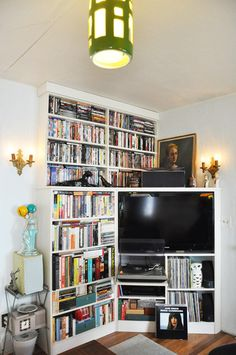 This is a really interesting idea for the living room.  The corner where our TV currently stands is a very awkward space, but something similar to this might help create more storage.  I'd want to put some doors and/or drawers on the bottom shelves the bookcase, though, to make it look less cluttered.