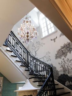 Bold wallpaper depicting a nature scene grabs your attention in this eclectic stairway. The black and white stairs coordinate beautifully with the walls, while a dazzling chandelier adds a hint of glamor overhead. Black And White Stairs, Black And White Wallpaper, Interior Design Your Home, Interior Decorating, Decorating Ideas, Decor Ideas, Bold Wallpaper, Beautiful Wallpaper, Wallpaper Ideas