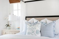Layered throw pillows in different patterns but similar shades of blue create subtle interest in this calm, coastal-style bedroom. The beautiful blue pillows pop against the crisp white bed linens.