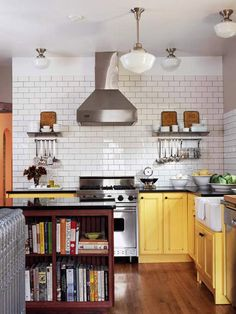 Yellow birch cabinets with a distressed finish make a colorful statement against walls of white subway tile. Adding black slab countertops and hardware guarantees that this period-style kitchen makes a strong style statement. Although neutral in color, the chimney hood's shapely silhouette makes it and the commercial-style range beneath a focal point.