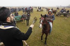 A priest blesses horses before beginning of annual race organized by Orthodox believers on Epiphany Day in Pietrosani