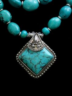 Stunning contemporary Tibetan Jewelry handcrafted by a family Tibetan Jewelry Artisans living in exile in Nepal. Quality made of a double row of real turquoise nuggets and pendant with silver and metal alloy accents. Elegant Fair Trade necklace.