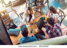 Group of young people sitting at a cafe, talking and enjoying, top view - stock photo