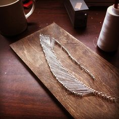 Use nails and string to make a feather.