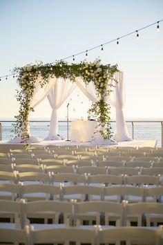 White Draped Jewish Wedding Ceremony Chuppah with Greenery and White Flowers