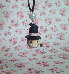 handmade polymer clay charm of turnip head from howls moving castle dangles on a waxed cotton black cord and is accented with a pearl bead for