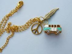 This is a gold colored long boho necklace. It is 70 cm (27,5 inch) long and has features three charms: a teal camper van/bus, a feather and a