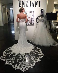 Enzoani fitted crepe strapless wedding dress with long lace illusion train and back detail. Available at www.theweddingdresscompany.co.uk