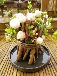 Holz und Blumen zusammenstecken und mit Bast oder dickem Garn zusammenhalten - Centrepiece fertig!