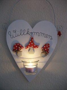 """Schild in Herzform mit der Aufschrift """"Willkommen"""" mit drei kleinen Fliegenpilzen und einem Teelicht, das durch einen stabilen Draht gehalten wird. Die Fliegenpilze werden wunderschön von der..."""