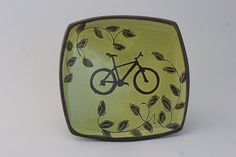 Celebrate bike love with this hand-built square tray!  Handmade ceramic platter for snacks, jewellery, keys, this and that. A nice piece to just hang on the wall and enjoy. Brightly coloured slip with hand-drawn mountain bike stencil and painted vines. Raised vine slip-trailed on the back on the back for extra fun.  I always recommend to hand-wash handmade items, but if necessary, it is dishwasher & microwave safe.  Approximately 5.25 x 5.25x 0.5 Rather have a different colour, different...