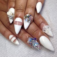White Stiletto Nails With Rhinestones and Flower Accents.