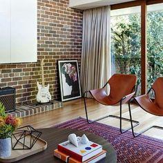 Sala de estar cool, com poltronas em couro, tapete colorido e mesa de centro em madeira. Parede em tijolo aparente e piso em laminado de madeira. Quadro e uma guitarra na decoração.