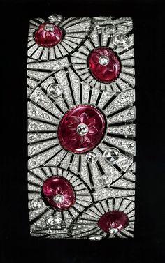 Cartier. Bracelet, 5 rubis gravés pour 40,91 carats, or gris , diamants taille rose de belle eau mélangés à des diamants taille brillant, et sous le rubis gravé du centre, une montre à quartz.Carved ruby and diamond art deco bracelet by Cartier.