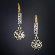 Few original antique diamond ear drops come as sweet and lovely as these exquisite jewels imported into France, circa 1890. A pair of bright-white old mine-cut diamonds, together weighing .75 carat, sparkle from within ornate platinum settings backed in 18K yellow gold and surmounted by gently curved rows of glittering rose-cut diamonds. 1 inch long, with French import marks.