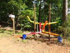 Ball Drop Game- Balls stored in the mailbox can be dropped into the four pipes and will come out in one of the buckets. This helps with gross motor skills and cognition. The station is built with 4 inch PVC drain pipe. It is suspended from 4x4x12 posts with brackets made from 2x4s