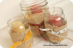 I have tons of baby food jars left over, but I also got a pint size mason jar for some of these too.  I filled them with some popcorn kernels and placed the candle inside.  I got some burlap and wrapped it around the jar and then added some ribbon.