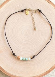 Add some POP to your choker collection! This choker features colored marble like beads on a faux leather strap. Absolutely the perfect compliment to any boho outfit! Features an adjustable gold link c