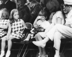 The restless tot is John Kennedy, son of the late President, and he is admonished by his mother Jacqueline Kennedy, weeps, and settles back to watch further proceedings.