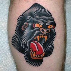 Angry Black Gorilla Tattoo With Red Tounge And Orange Eyes For Men On Calf