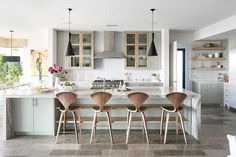 Well appointed contemporary kitchen features two Tom Dixon Beat Tall Lights hung over a long light gray island accented with a gray and white quartzite waterfall countertop seating Cherner Counter Stools in front of stacked under counter blond wood shelves.