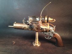 SOLD   BLUE ETHER PEACEMAKER--Another Steampunk Pistol has emerged from the sequestered laboratories of Prof Archibald Q. Tinkerman. Drawing from the technologies evolving after the Cowboy and Alien War, the Blue Ether Peacemaker is a powerful protective tool for the modern day adventurer. The pistol cocks and fires and the Blue Ether Ray is activated with a full trigger pull. This one-of-a-kind, desk sculpture is signed and dated by the artist and can be used for display, to compliment…