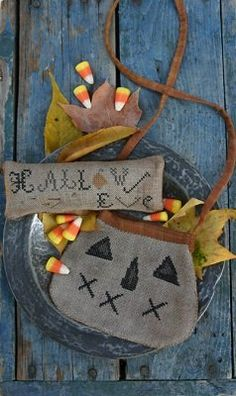 A delightful Halloween cross stitch pattern that you stitch and finish into a treat bag and pinkeep from Stacy Nash Primitives. The cross st...