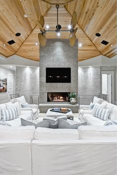 Vaulted Wood ceiling, Grey tile and concrete fireplace focal point. beach chic slip covered sectional. Designed by architect Michelle Balfoortn interiors by Beach Chic Design, Ponte Vedra Beach, Florida. Photo byAdam Cohen.
