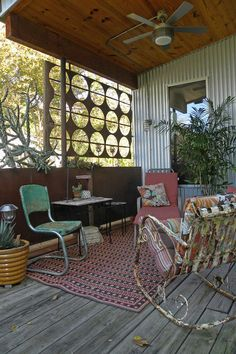 This front porch has an eclectic mix of vintage patio furniture, ethnic textiles and architectural elements, like a sheet-metal privacy screen with a punched-out circular pattern. Shabby Chic Style, Shabby Chic Veranda, Vintage Patio Furniture, Salvaged Furniture, Lawn Furniture, Outdoor Furniture, Furniture Design, Corrugated Wall, Outdoor Rooms