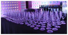 Copas alineadas, mantelería negra, reflejos violáceos de la iluminación en el cristal... Ambiente perfecto.