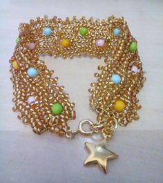 Pulseira em miçangas douradas com bolinhas coloridas e acabamento dourado.Feita à mão.