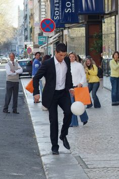 Soccer Player Cristiano Ronaldo  (CR7) juggling a ball in the streets while the public goes nuts.  Ummm....I could get use to soccer!