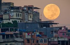 The moon appears behind the Mare shanty town complex in Rio de Janeiro on May 6, 2012. (Victor R. Caivano/Associated Press) #