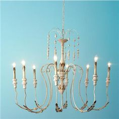 Italian Antique Reproduction Tassel Chandelier  We have the right look in antique reproductions at the right price! This 8-light Italian-inspired chandelier is finished in a pale cream with hints of aged rust. The iron loop arms gracefully extend out with acanthus leaf accents. Carved tassels dangle delicately from the waterfall top.